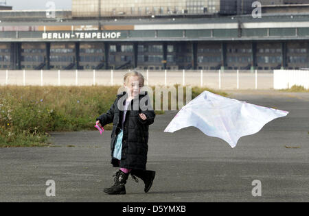 A little girl tries to let her kite fly on the former Tempelhof airport in Berlin, Germany, 22 September 2012. Photo: - Stock Photo