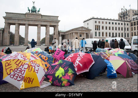 A group of asylum-seeking refugees gather in front of vans at Brandenburg Gate in Berlin, Germany, 01 November 2012. - Stock Photo