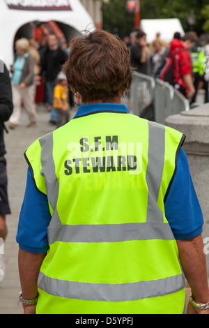 rear view woman wearing  of high viz jacket  with words steward - Stock Photo
