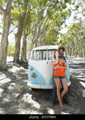 Young Couple in Front of Camper Van - Stock Photo