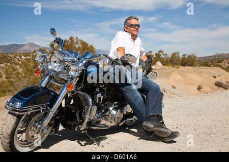 Senior man leaning motorcycle desert road - Stock Photo