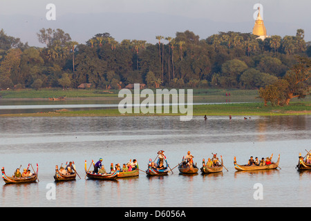 Tourist boats lining up on Taungthaman Lake, Myanmar, to view sunset over U Bein Teak Bridge 5 - Stock Photo