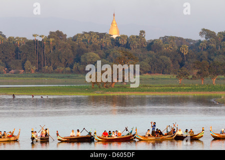 Tourist boats lining up on Taungthaman Lake, Myanmar, to view sunset over U Bein Teak Bridge 1 - Stock Photo