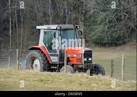 A tractor traveling along a countryside farm  track - Stock Photo