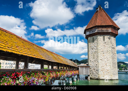 A view of the famous wooden Chapel Bridge of Luzern, Lucerne in Switzerland, with the tower in foreground - Stock Photo