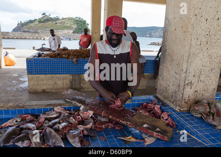 Local fisherman gutting and cleaning fish heads at the harbour market in Micoud, St Lucia - Stock Photo