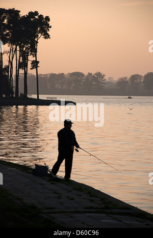 Silhouette of man fishing at dusk - Stock Photo