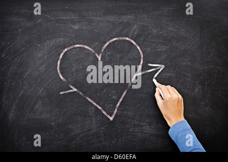 Hand drawing heart with chalk on chalkboard - love concept - Stock Photo