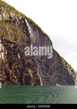 The towering cliffs of the Geiranger Fjord made larger by small ferry,Norway - Stock Photo