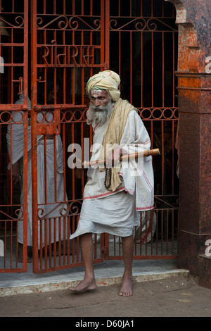 A Hindu Sadhu stands at the entrance to a shrine at the South door of the Jaggarnath temple in Puri, Odisha, India - Stock Photo