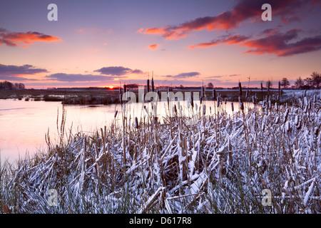 dramatic sunrise over frozen lake - Stock Photo
