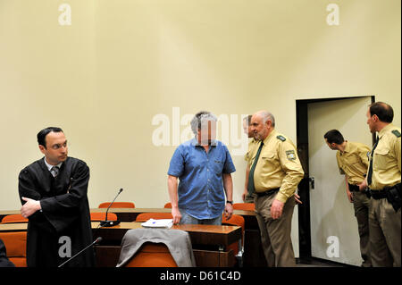 The 51 year old defendant Thomas S. stands next to judical staff and his lawyer Adam Ahmed (L) in the court room - Stock Photo