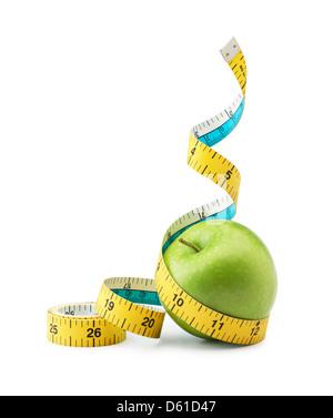 tape measure measuring green apple against white background - Stock Photo