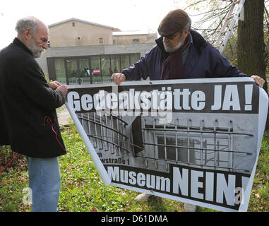 Dirk Jungnickel (L) and Bob Bahra put up a protest poster in front of the memorial site Leistikowstraße in Potsdam, - Stock Photo