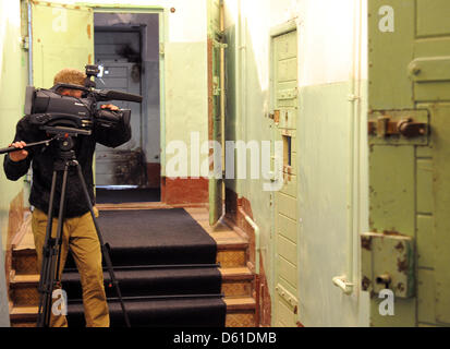 A camera man films the cells in the cellar of the memorial site Leistikowstraße in Potsdam, Germany, 18 April 2012. - Stock Photo