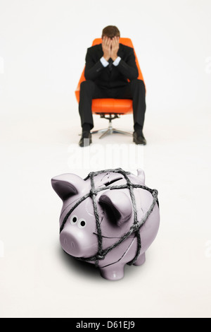 Worried businessman chair piggybank tied with rope representing financial difficulties - Stock Photo