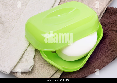 Soap In Container Sitting On Face Towels - Stock Photo