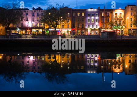 Horizontal view of the colourful buildings along Batchelor's Walk reflected in the River Liffey in Dublin at night. - Stock Photo