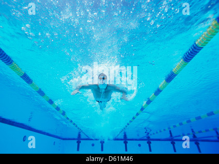 Underwater shot of male swimmer swimming in pool - Stock Photo