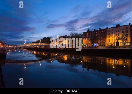 Horizontal view of the Ha'Penny Bridge aka Droichead na Leathphingine or Liffey bridge in Dublin at sunset. - Stock Photo