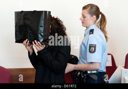 A defendant hides behind a bag before the trial at the Regional Court in Detmold, Germany, 30 April 2012. Five siblilngs - Stock Photo