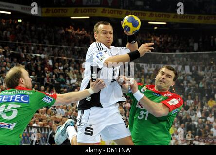 Kiel's Christian Zeitz (C) gets past Magdeburg's Yves Grafenhorst and Bartosz Jurecki during the handball Bundesliga - Stock Photo