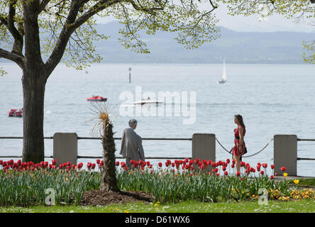 People walk along the waterfront of Lake Constance in Friedrichshafen, Germany, 28 April 2012 Meteorologists predict - Stock Photo