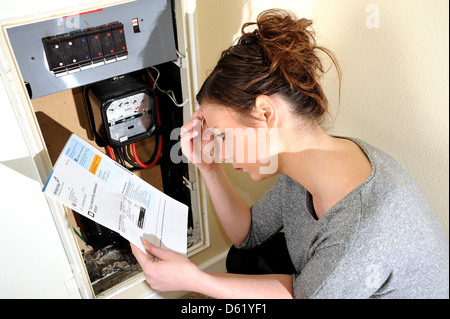 Young woman 20s attempting to read and understand her electricity meter reading and energy bill - Stock Photo