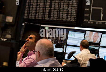 Brokers sit in front of the display panel showing the horizontal and falling graph of the German stock market index, - Stock Photo