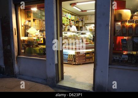 Shopkeeper in delicatessen at night, Via Garibaldi, Castello, Venice, Italy - Stock Photo