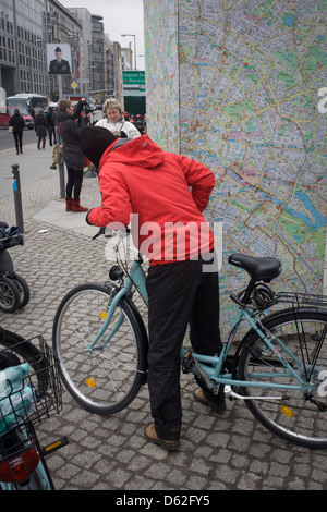 A cyclist stops to read a map of Berlin near the former Checkpoint Charlie, the former border between Communist - Stock Photo