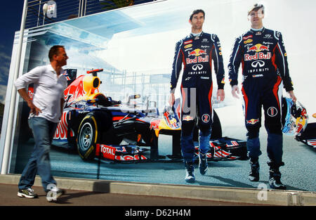 A man walks in front of a billboard on the floating motor home of Red Bull with the images of German Formula One driver Sebastian Vettel (L) and Mark Webber (R) prior to the Formula One Grand Prix of Monaco in Monte Carlo, Monaco, 22 May 2012. The Grand Prix will take place on 27 May. Photo: Jens Buettner dpa
