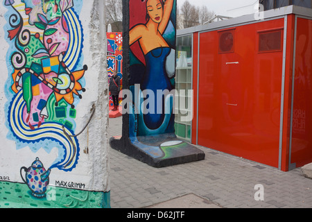 Colourfully-painted sections of the old Berlin Wall are exhibited by local artists opposite the former Checkpoint - Stock Photo