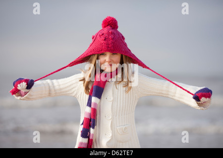 Portrait of a cute young girl in pink hat and Winter clothing on beach at Hunstanton, Norfolk, UK - Stock Photo
