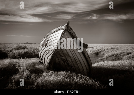 Lonely old wooden fishing boat on the saltmarshes at Burnham Deepdale in Norfolk, UK - Stock Photo