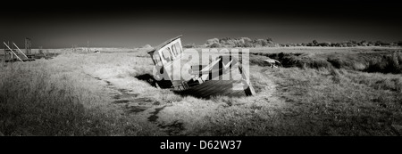 Panoramic view of old wooden fishing boat washed up on the salt marshes at Thornham in Norfolk, England, UK. - Stock Photo
