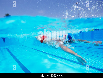 Professional male thlete swimming in pool - Stock Photo