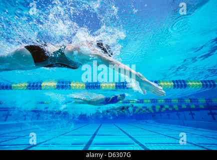 Four female swimmers racing together in swimming pool - Stock Photo