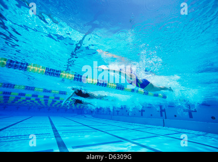 Group of female swimmers racing together in swimming pool - Stock Photo