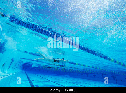 Swimmers racing together in swimming pool - Stock Photo
