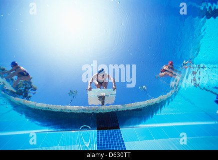 Low ngle view of female swimmers ready dive in pool from starting position - Stock Photo