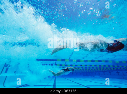 Young Caucasian female swimmers swimming in pool - Stock Photo