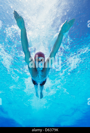 Professional young male thlete swimming in pool - Stock Photo