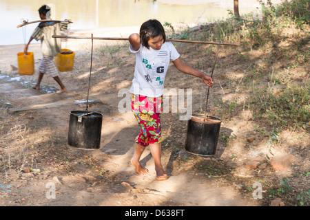 Young girl carrying a pannier filled with water, Minnanthu, Bagan, Myanmar, (Burma) - Stock Photo