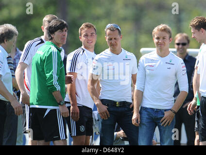 German Formula One racing drivers Michael Schumacher (4-R) and Nico Rosberg (3-R) visit a training session of the - Stock Photo