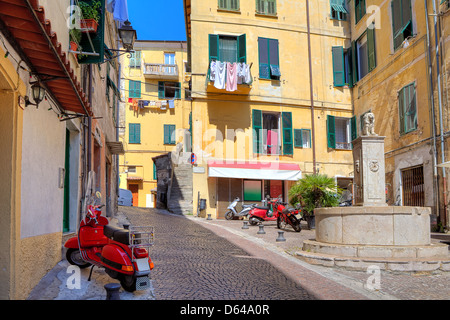 Typical view of small cobblestone street with scooters among old colorful residential buildings in town of Ventimiglia, - Stock Photo