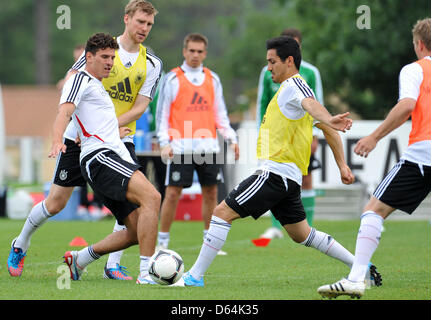 Germany's Mario Gomez (L-R), Per Mertesacker and Ilkay Gundogan vie for the ball during practice on a pitch in Tourettes, - Stock Photo