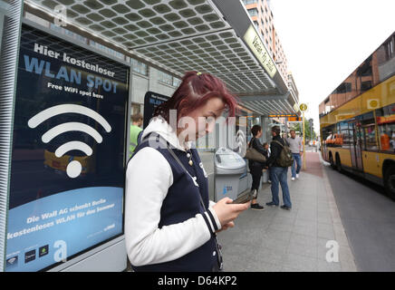 Melissa uses a free WLAN Spot next to a bus stop at Potsdamer Platz in Berlin, Germany, 30 May 2012. There will - Stock Photo