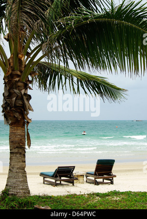 2 two deck chairs / sun lounges on the indonesian beach under a palm tree - Stock Photo