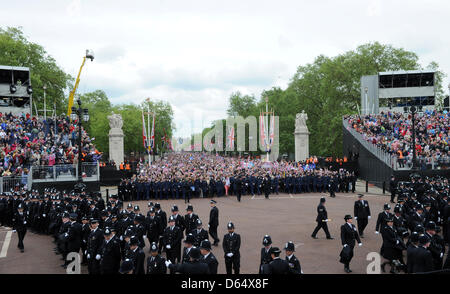 Policemen and cadets stop the crowd moving closer to see Queen Elizabeth II on the balcony of Buckingham Palace - Stock Photo